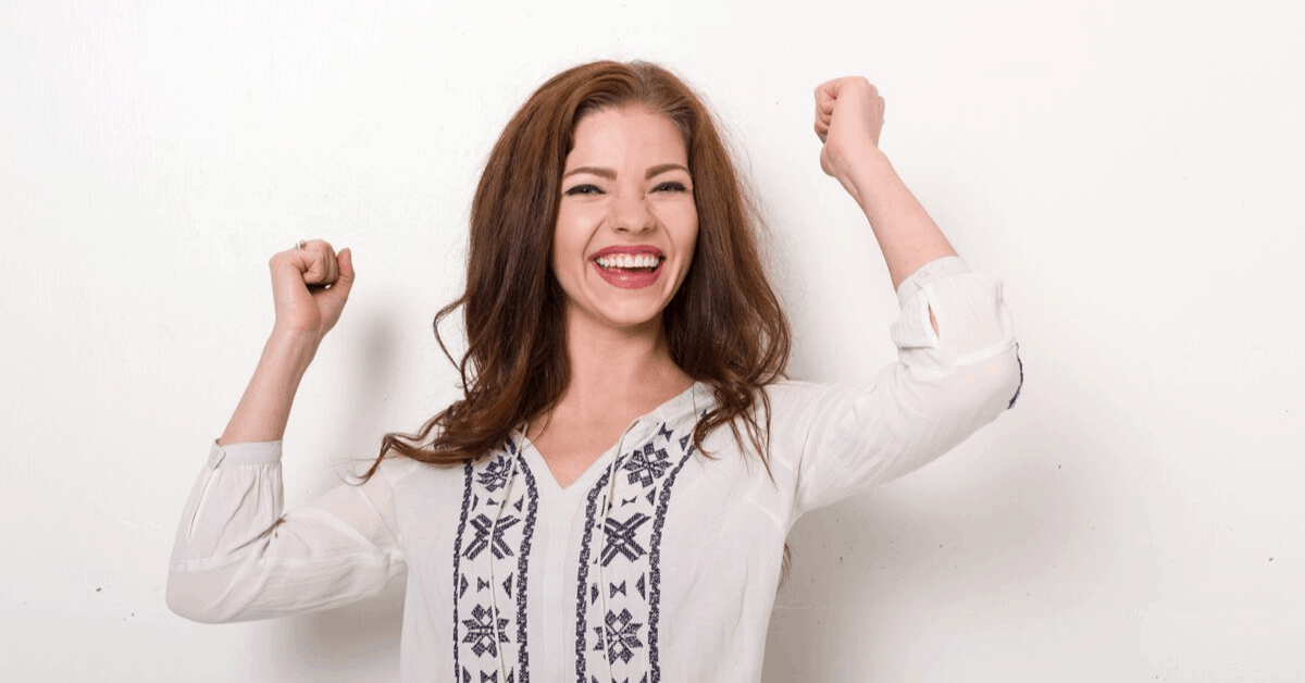 Lady smiling wide with both hands in the air