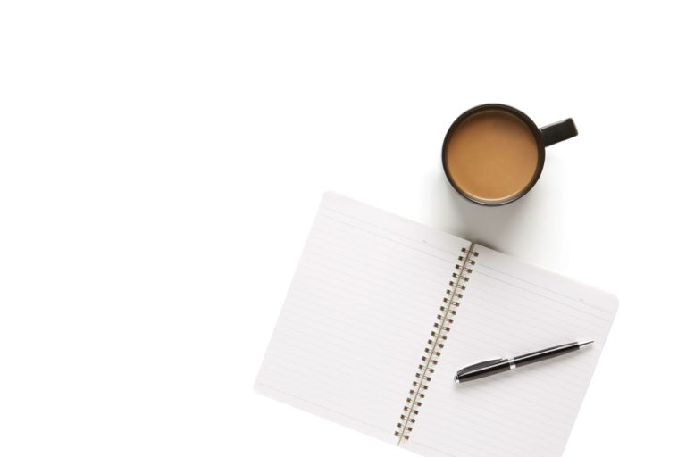 Pen and an open notebook beside a cup of coffee