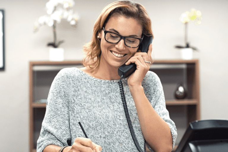Smiling woman taking down notes while talking on the phone