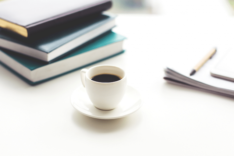 cup of coffee between books and paper
