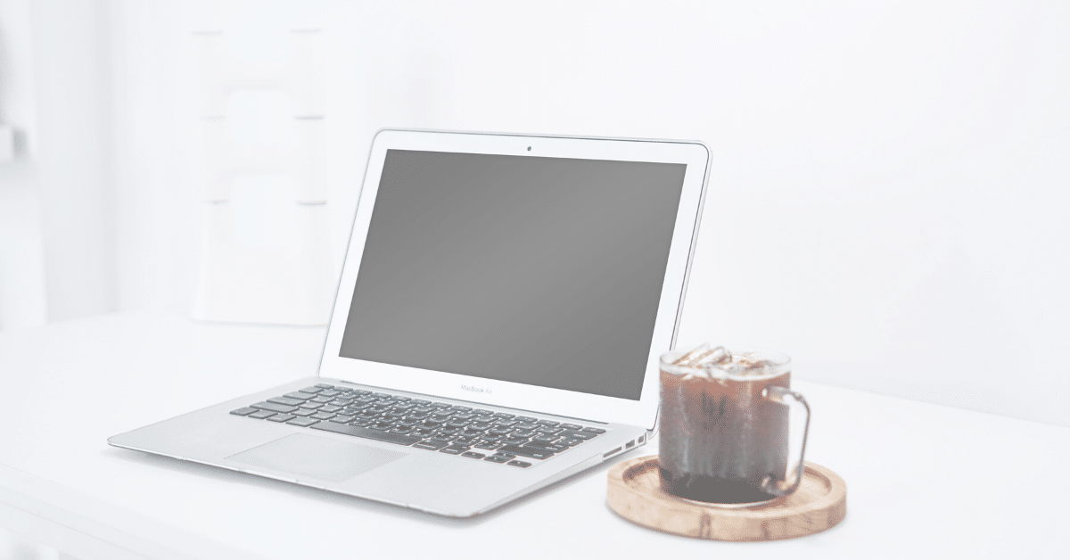 faded image of laptop beside an iced drink