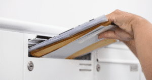 hand inserting mails into a mailbox