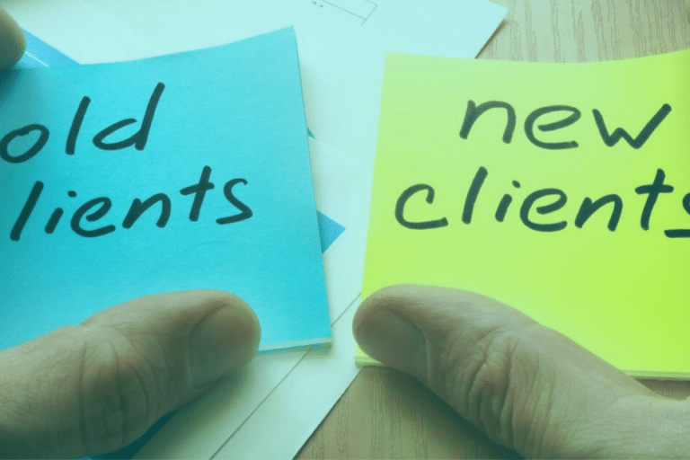 hands holding two sticky notes with old clients and new clients written on them