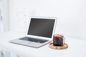 laptop beside an iced drink