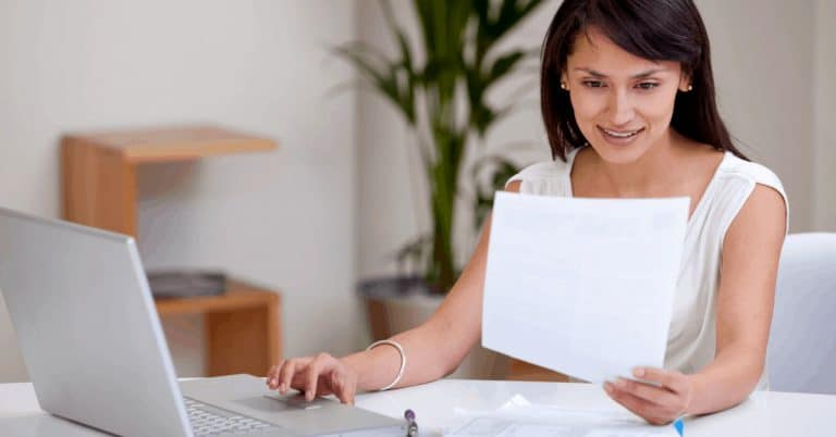 smiling woman looking looking at a paper while using laptop