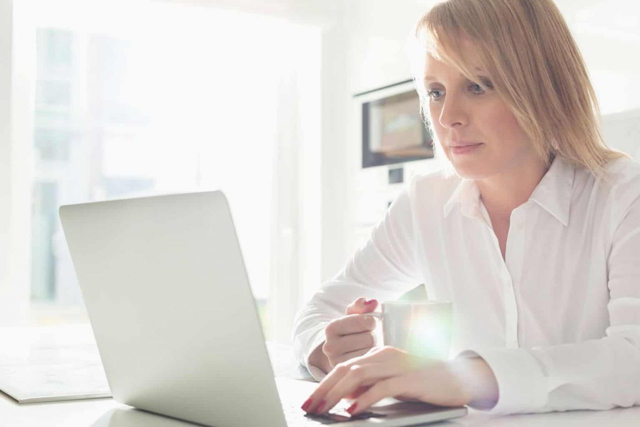 woman using a laptop while holding a mug