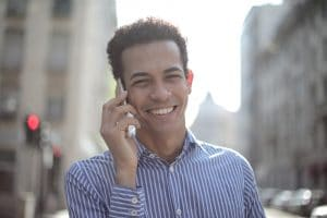 cheerful ethnic man talking on smartphone