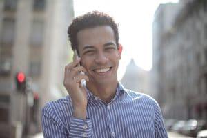 cheerful ethnic man talking on smartphone