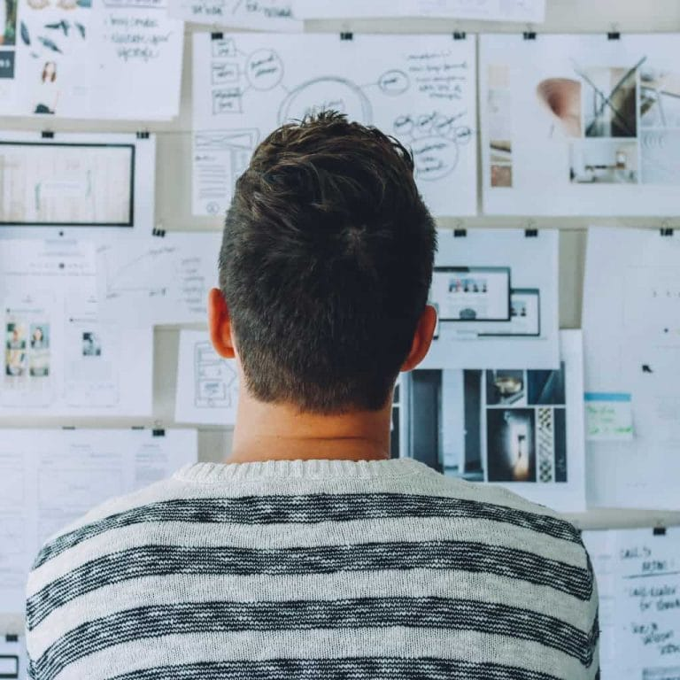 man looking at wall of business plans